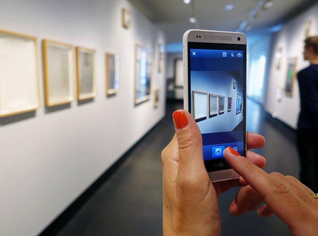 Frau macht im Museum Foto mit Handy