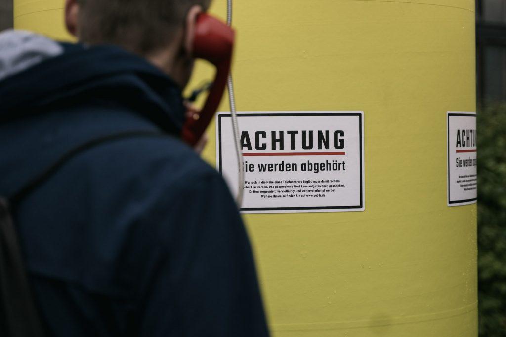 Ein Mann mit Telefonhörer am Ohr blickt auf Schild