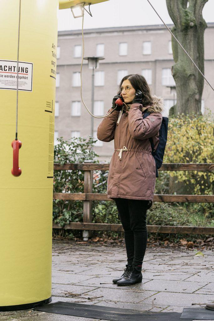 Frau steht vor der Installation mit Hörer am Ohr