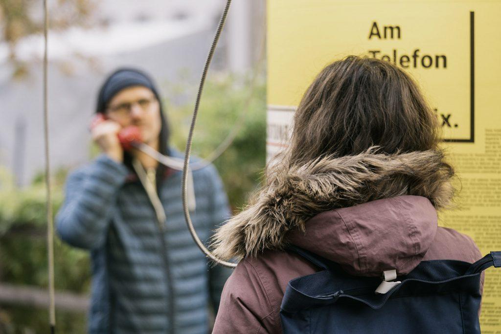 Mann und Frau halten rote Hörer ans Ohr